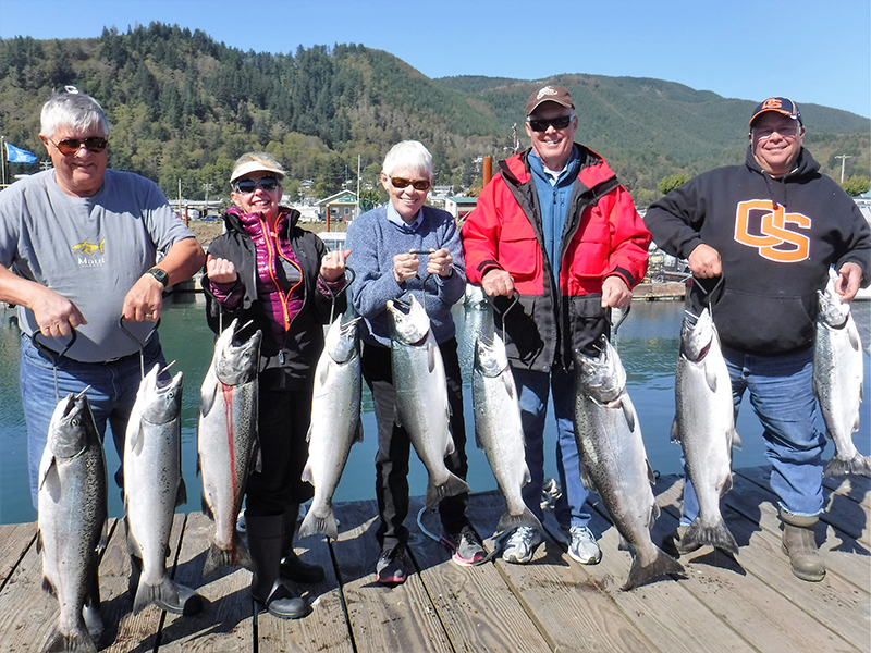 Men and Women with their Catch of the Day - Oregon Fishing Season Calendar - St. Laurent Guide Service