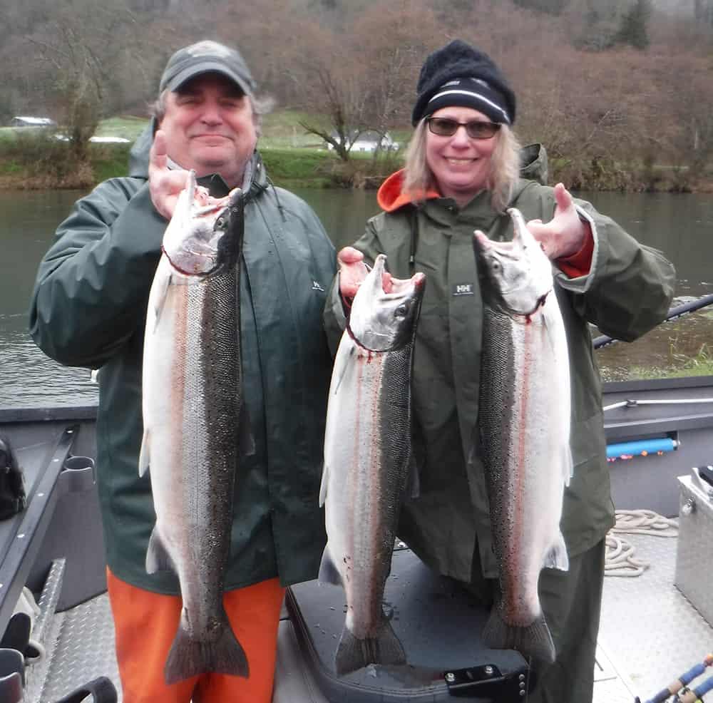 Couple in rain gear with Winter Steelhead - North Oregon Coast - St. Laurent Guide Service